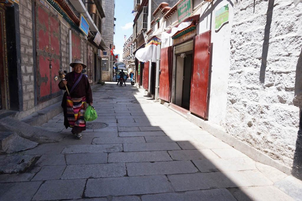 woman turning her prayer wheel in Lhasa during Tibet tour