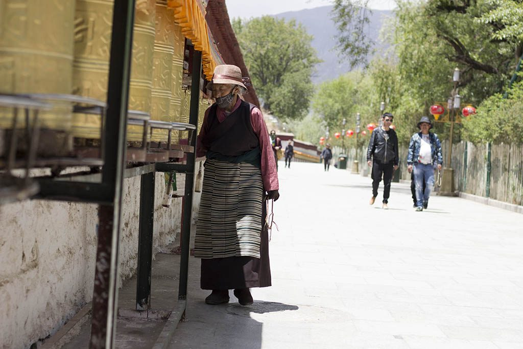 Woman turning the prayer wheels outside the potala palace